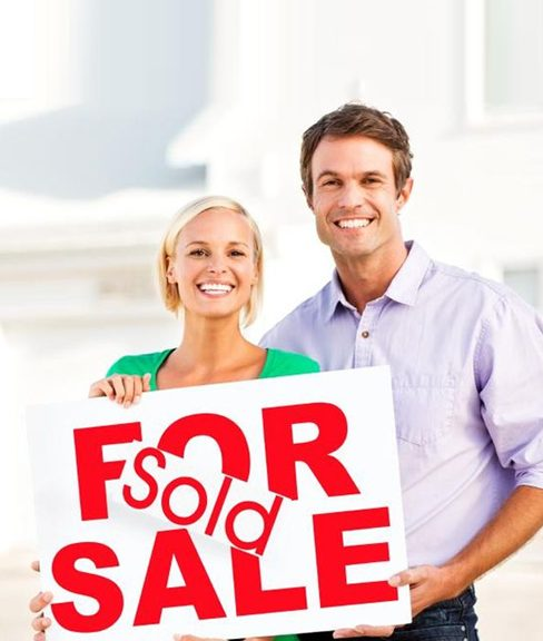 couple holding for sale sign sold